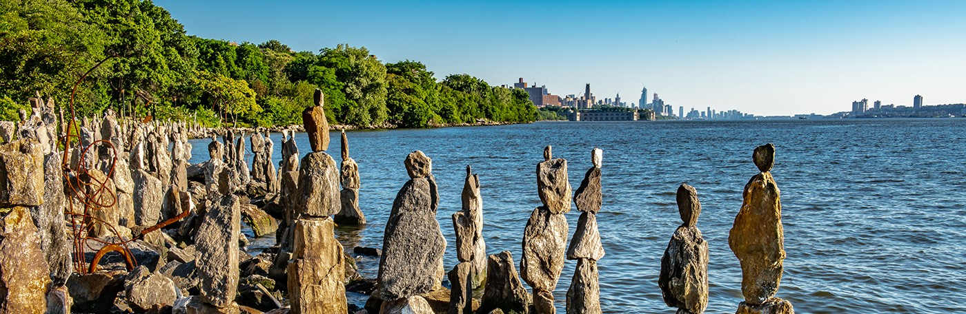 stone sculptures alongside the bank of the Hudson River with the Manhattan skyline in the background